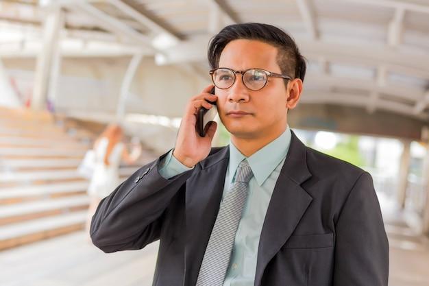 Homem de negócios considerável novo de ásia com seu smartphone que está na passagem da cidade moderna. Foto Premium
