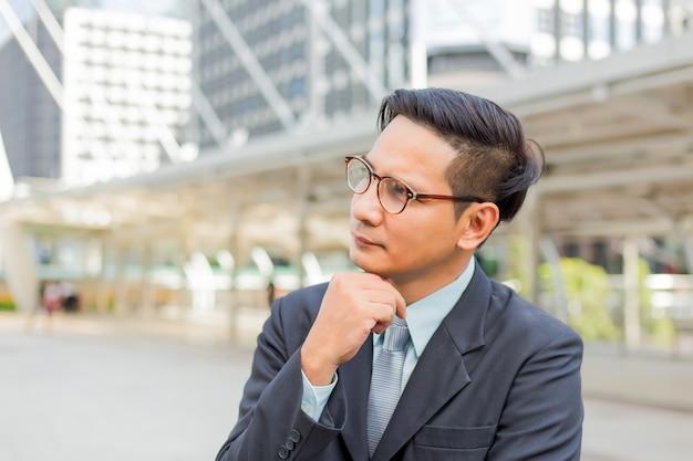 Homem de negócios considerável novo de ásia que pensa sobre seu negócio Foto Premium