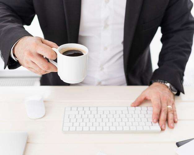 Homem de negócios de alto ângulo, desfrutando de uma xícara de café Foto gratuita