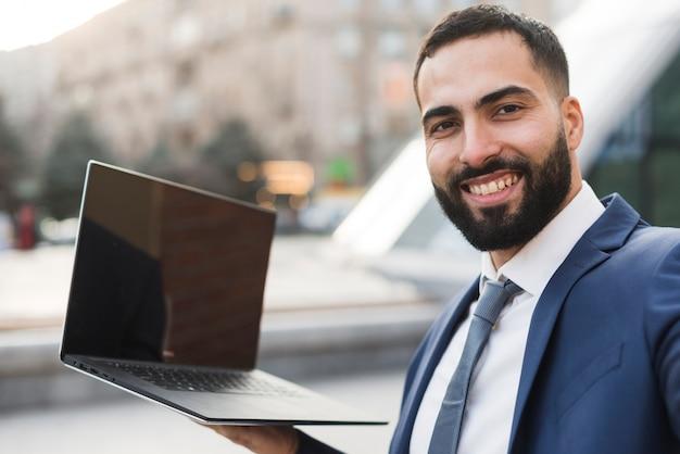Homem de negócios de baixo ângulo com laptop Foto gratuita