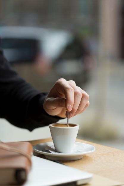 Homem de negócios de close-up a gostar de café Foto gratuita