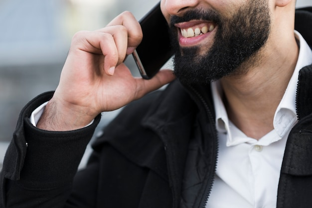Homem de negócios de close-up falando por telefone Foto gratuita