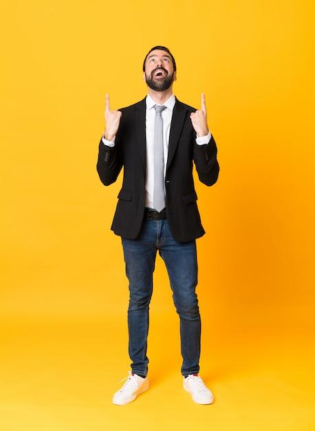 Homem de negócios de comprimento total sobre parede amarela isolada surpreso e apontando para cima Foto Premium