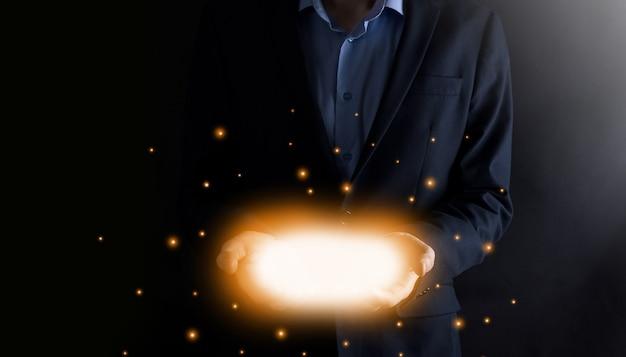 Homem de negócios de mãos abertas com luzes brilhantes em fundo escuro. Foto Premium