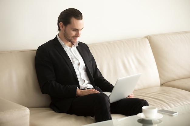 Homem de negócios de sorriso que trabalha no portátil remotamente da casa. Foto gratuita