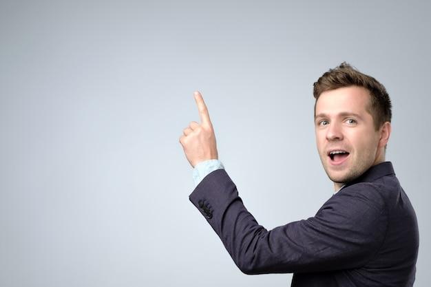 Homem de negócios de terno apontando para cima e sorrindo para a câmera Foto Premium