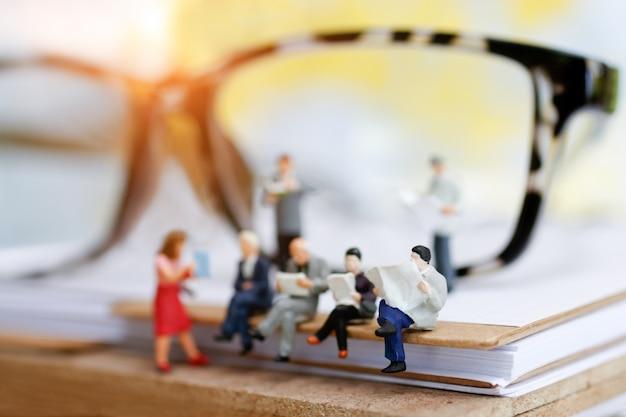 Homem de negócios diminuto que senta-se em livros. Foto Premium