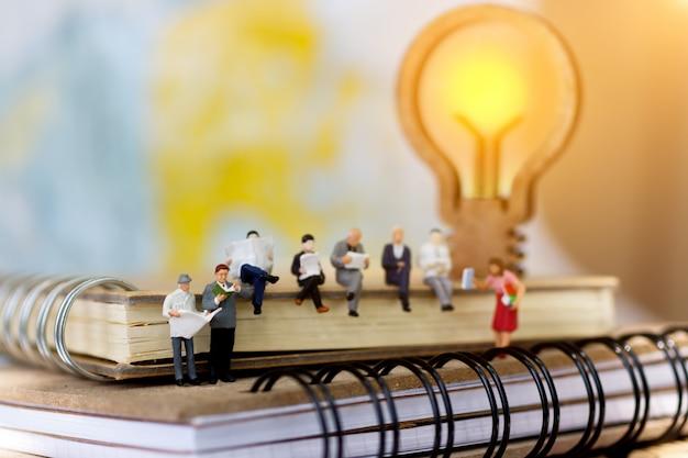 Homem de negócios diminuto que senta-se no livro com lâmpada. Foto Premium