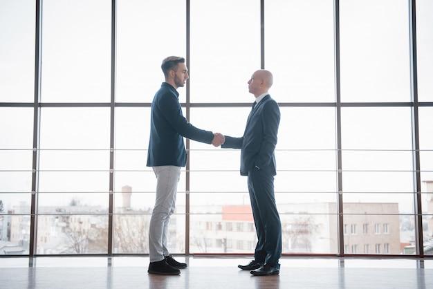 Homem de negócios dois confiante, apertando as mãos durante uma reunião no escritório Foto Premium