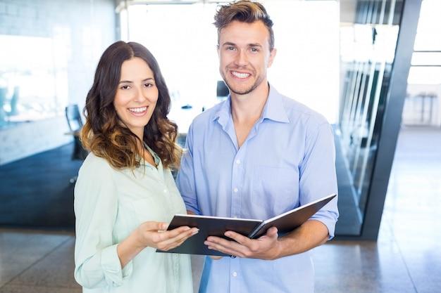 Homem de negócios e mulher de negócios interagindo segurando organizador no escritório Foto Premium