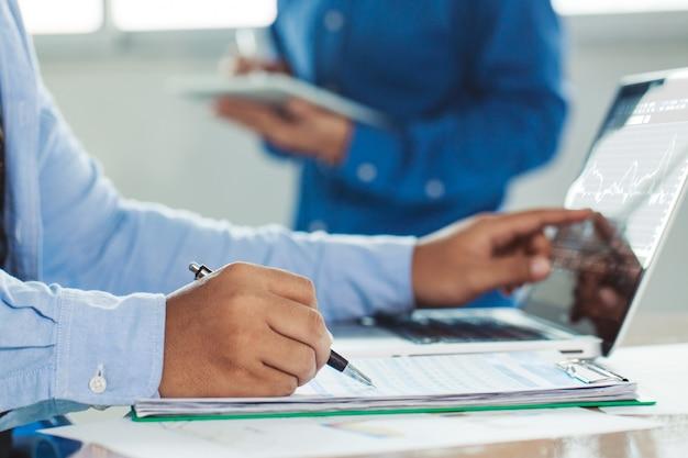 Homem de negócios elegante que trabalha em seu portátil no escritório, analisando dados e gráfico, homem novo que datilografa no computador que senta-se na tabela de madeira. Foto Premium