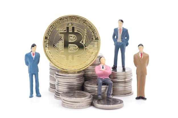 Homem de negócios em miniatura e bitcoin em fundo branco Foto Premium