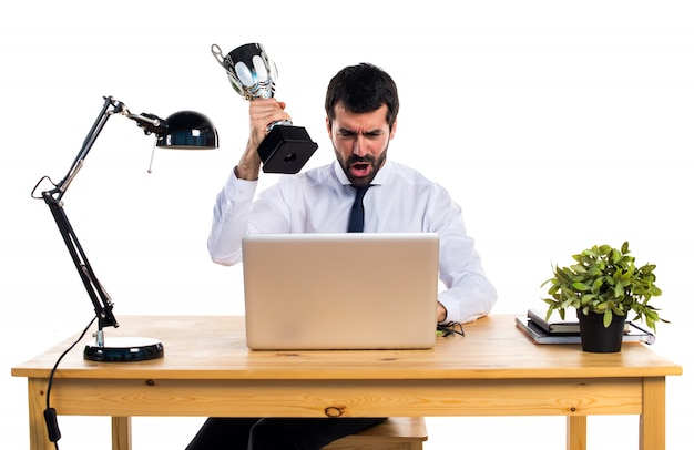 Homem de negócios em seu escritório segurando um troféu Foto gratuita