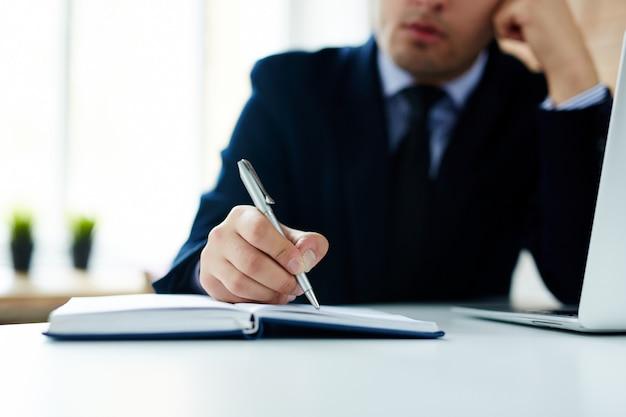 Homem de negócios, escrevendo no caderno diário Foto gratuita