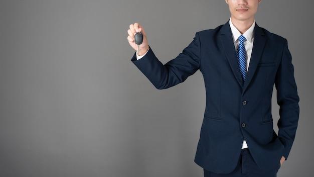 Homem de negócios está segurando a chave do carro, fundo cinza no estúdio Foto Premium