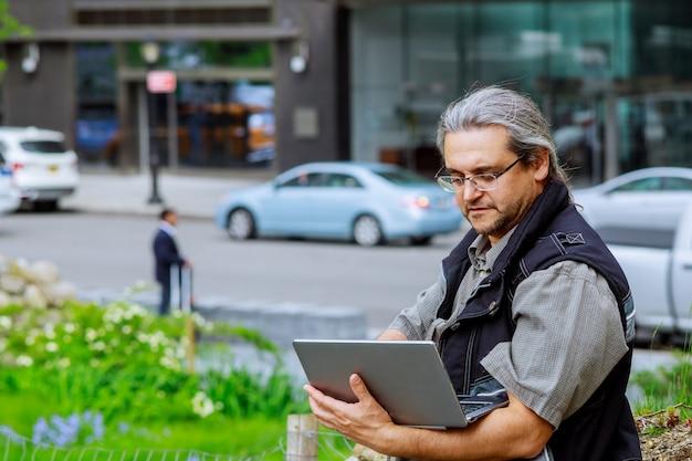 Homem de negócios europeu viajando, trabalhando em nova york com os cabelos grisalhos, trabalhando no computador portátil Foto Premium