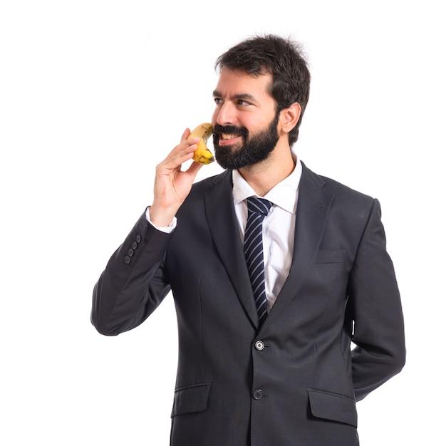 Homem de negócios falando por banana sobre fundo branco Foto gratuita