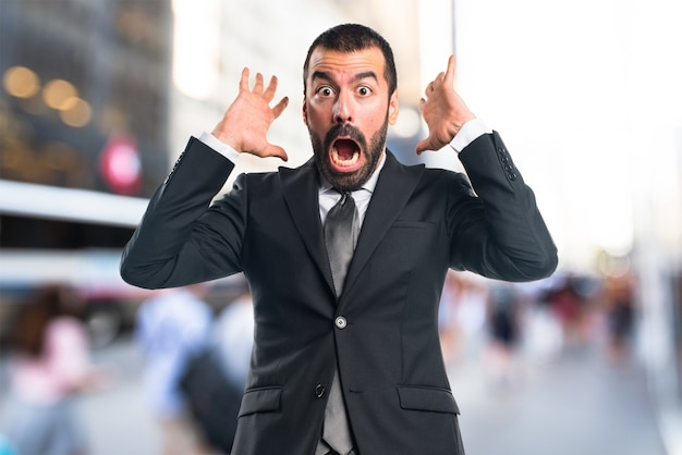 Homem de negócios fazendo um gesto de surpresa com um fundo sem foco Foto Premium