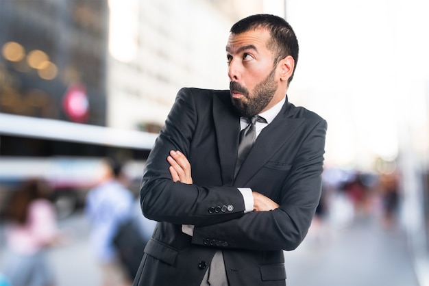 Homem de negócios fazendo um gesto sem importância em um plano de fundo sem foco Foto Premium
