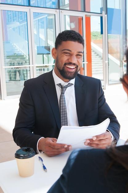 Homem de negócios feliz discutindo documentos com o parceiro no café Foto gratuita