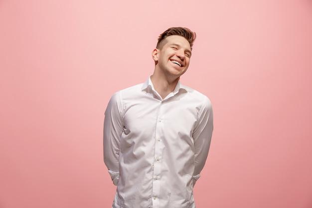 Homem de negócios feliz em pé e sorrindo contra fundo rosa. Foto gratuita