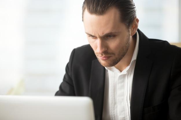 Homem de negócios focalizado olhando na tela do laptop Foto gratuita