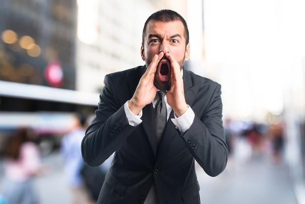 Homem de negócios gritando em fundo não focado Foto Premium