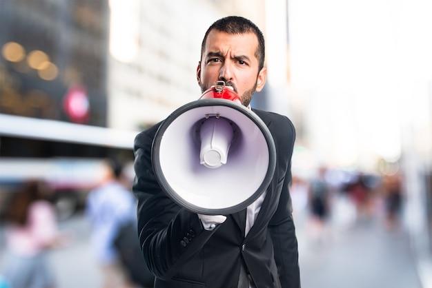 Homem de negócios gritando por megafone em fundo não focado Foto Premium