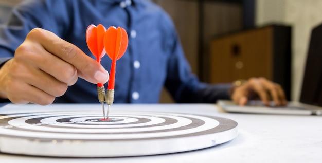 Homem de negócios guardando dardos visando o centro do alvo, conceito do sucesso do crescimento do negócio. Foto Premium