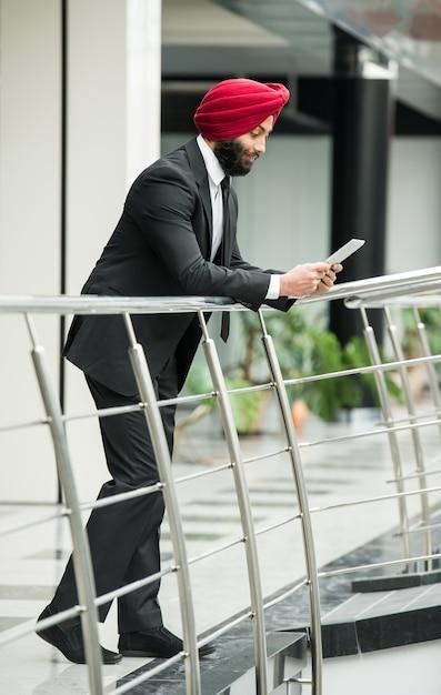 Homem de negócios indiano novo no escritório moderno com tabuleta. Foto Premium