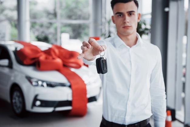 Homem de negócios jovem com as chaves nas mãos, compra um carro na cabine. Foto Premium