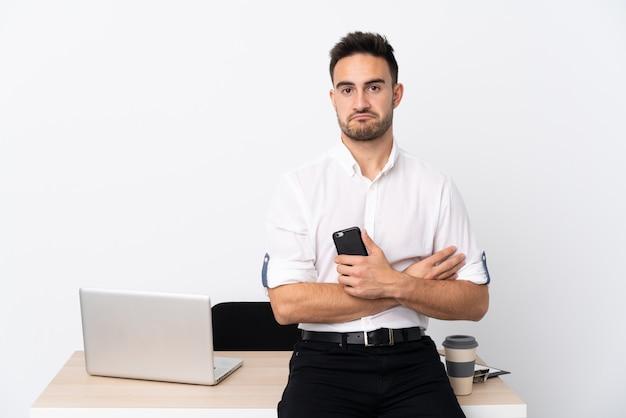 Homem de negócios jovem com um telefone móvel em um local de trabalho triste Foto Premium