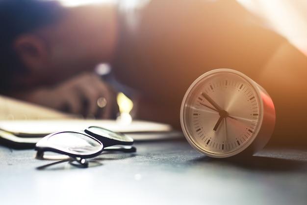 Homem de negócios jovem dormindo na mesa do escritório Foto Premium