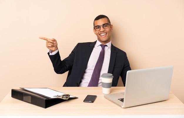 Homem de negócios jovem em seu escritório com um laptop e outros documentos, apontando o dedo para o lado e apresentando um produto Foto Premium