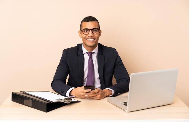 Homem de negócios jovem em seu escritório com um laptop e outros documentos enviando uma mensagem com o celular Foto Premium