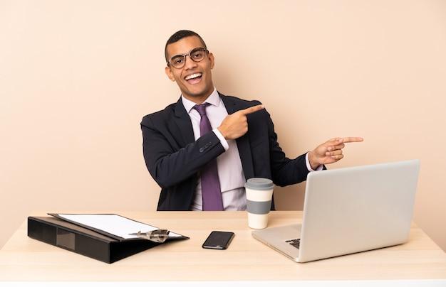 Homem de negócios jovem em seu escritório com um laptop e outros documentos surpreso e apontando o lado Foto Premium