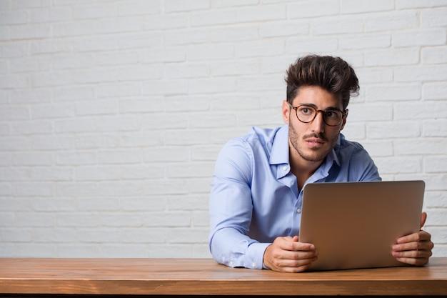 Homem de negócios jovem sentado e trabalhando em um laptop preocupado e oprimido, esquecido, perceber algo, expressão de choque por ter cometido um erro Foto Premium