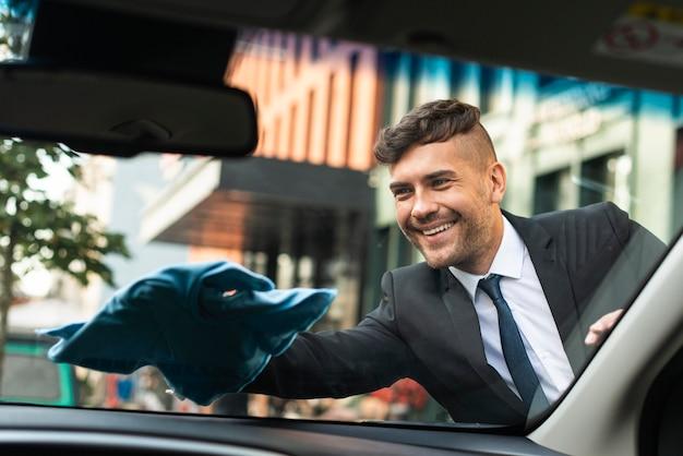 Homem de negócios limpando o carro Foto Premium