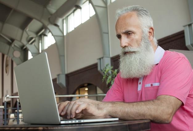 Homem de negócios maduros sênior tomando um café em uma cafeteria e trabalhando em seu laptop Foto Premium