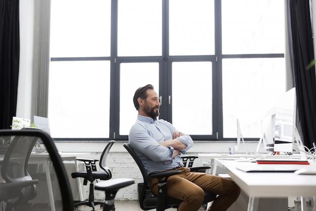 Homem de negócios maduros, sentado em uma cadeira com os braços cruzados Foto gratuita