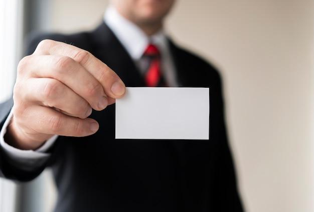 Homem de negócios, mantendo o cartão de visita em branco Foto gratuita