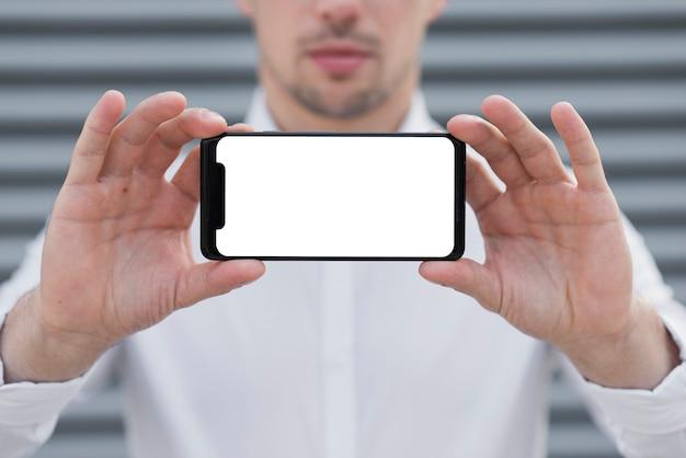 Homem de negócios, mantendo o modelo de iphone Foto gratuita