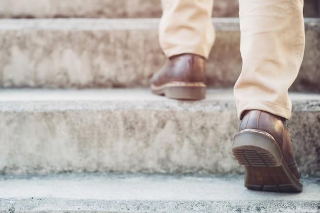 Homem de negócios moderno que trabalha os pés do close-up que andam acima das escadas na cidade moderna. Foto Premium
