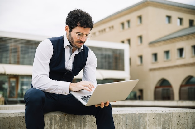 Homem de negócios moderno usando laptop ao ar livre Foto gratuita