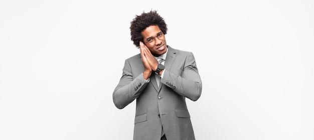 Homem de negócios negro afro se sentindo apaixonado e parecendo fofo, adorável e feliz, sorrindo romanticamente com as mãos ao lado do rosto Foto Premium