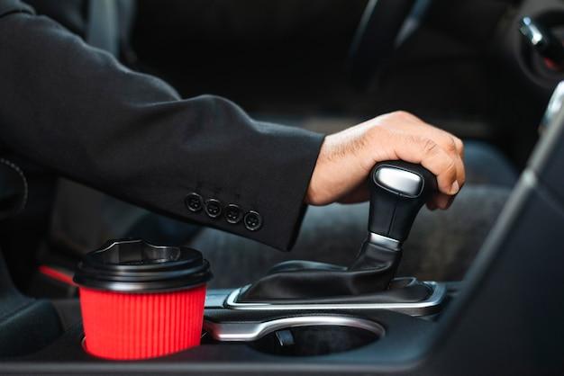 Homem de negócios no carro trocando as marchas Foto Premium