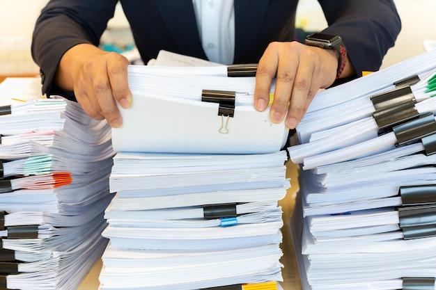 Homem de negócios no terno olhar através da pilha de documentos no escritório. Foto Premium