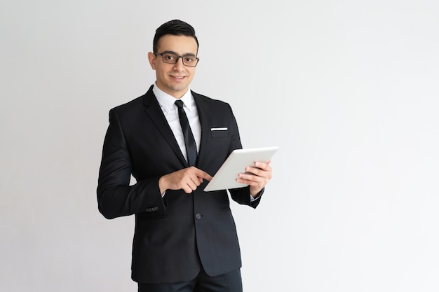 Homem de negócios novo alegre que verifica o email na tabuleta e que olha a câmera. Foto gratuita