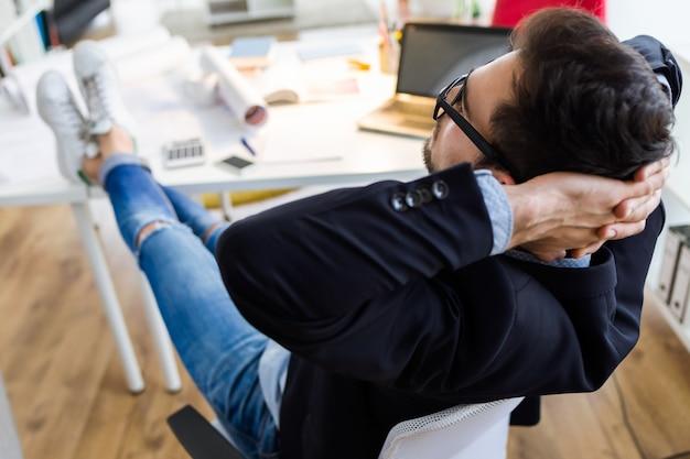 Homem de negócios novo considerável que relaxa um momento no escritório. Foto gratuita