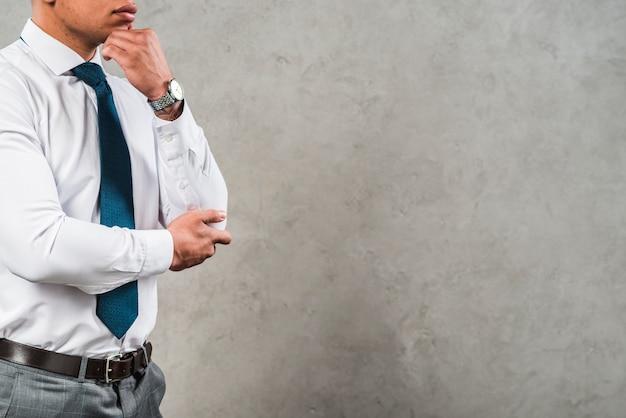 Homem de negócios novo contemplado no formalwear que está contra o muro de cimento cinzento Foto gratuita